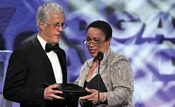 President Michael Apted accepts the Dramatic Series Night Award from S. Epatha Merkerson.